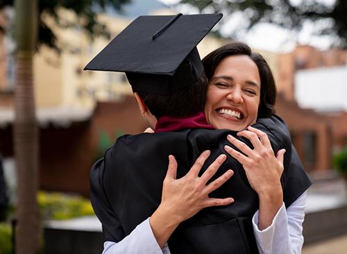 Hispanic mom hugs college graduate son