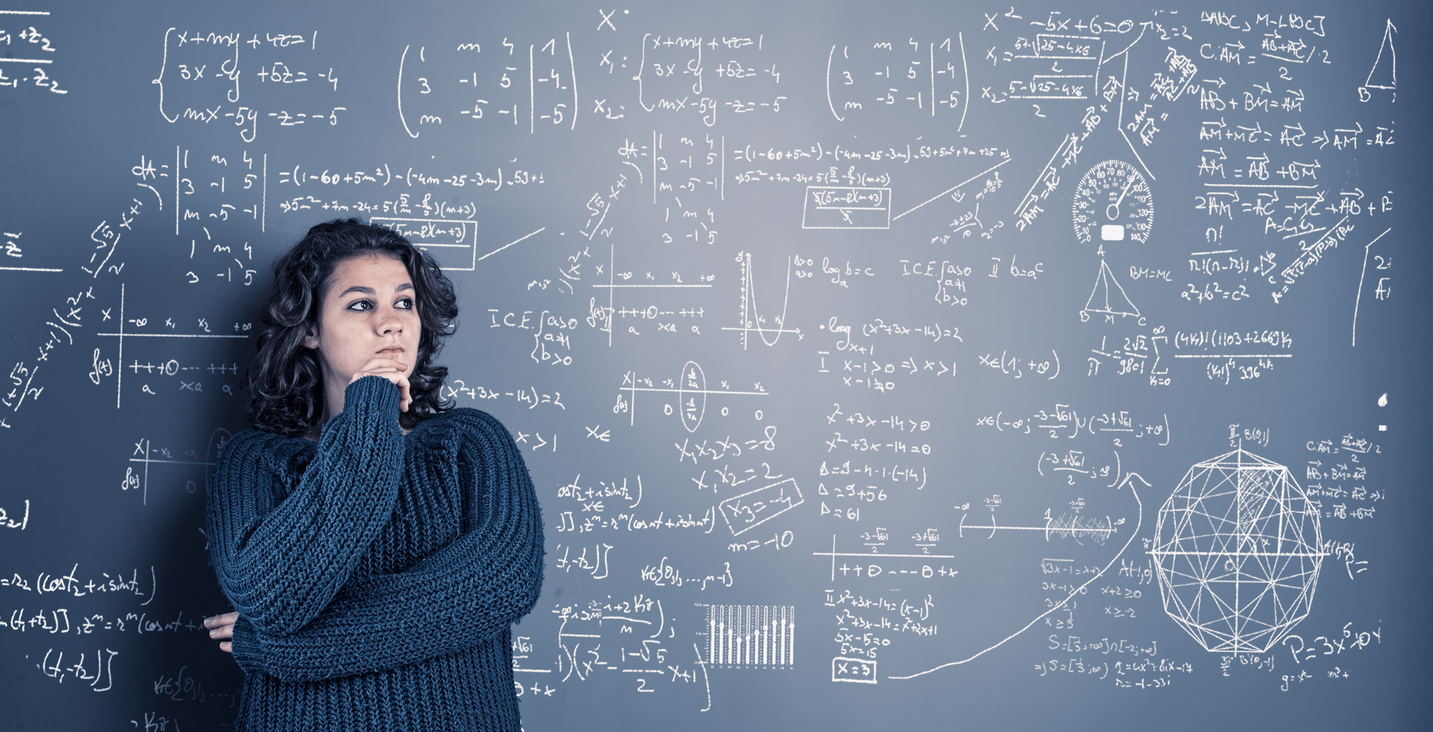 Female college student stands in front of blackboard with math problems written on it