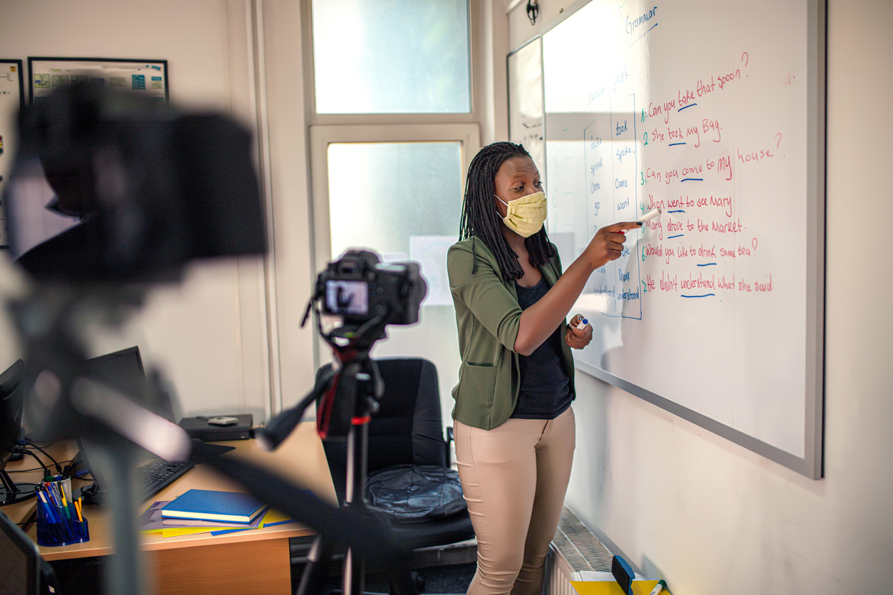 Young black woman standing near whiteboard while teaching online
